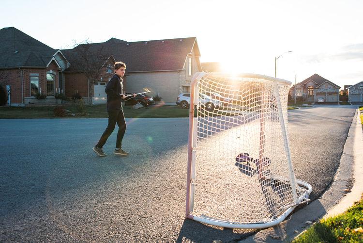 Full length of man playing soccer against sky