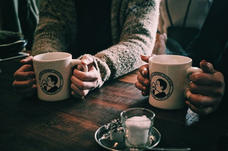 Drink Human Hand Hand Cup Food And Drink Mug Coffee Refreshment Coffee - Drink Coffee Cup Holding Real People Leisure Activity Human Body Part Midsection Lifestyles People Indoors  Two People Sitting