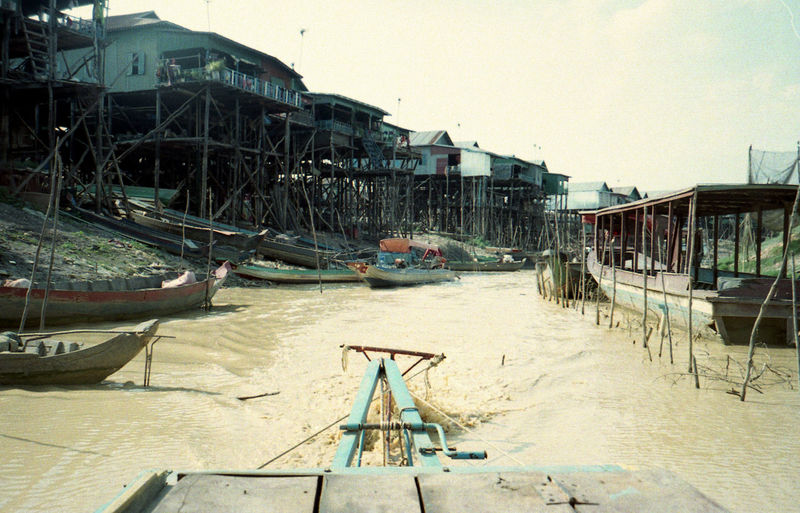 Boats moored on beach by buildings against sky