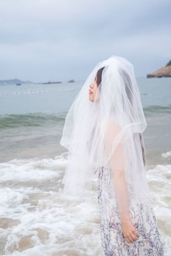 Side View Of Young Bride Wearing Veil At Beach