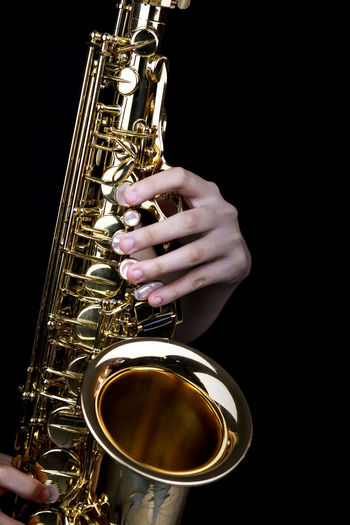 Music Instrument Alto Saxophone Player, Saxophone Player Isolated on black Music Musical Instrument Human Hand Hand Arts Culture And Entertainment Brass Instrument  One Person Musician Human Body Part Artist Performance Saxophone Gold Colored Studio Shot Playing Metal Holding Jazz Music Brass Skill  Black Background Finger