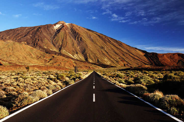 Empty road leading towards mountains against sky at teide national park