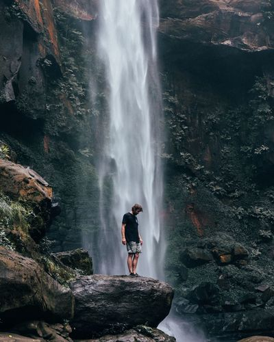 Man Standing By Waterfall On Rock
