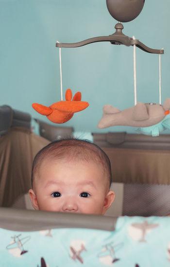 Portrait Of Baby Peeking From Crib
