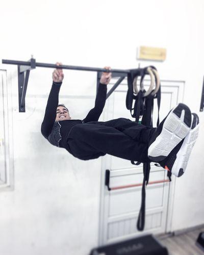 Full length of man hanging on bar in gym