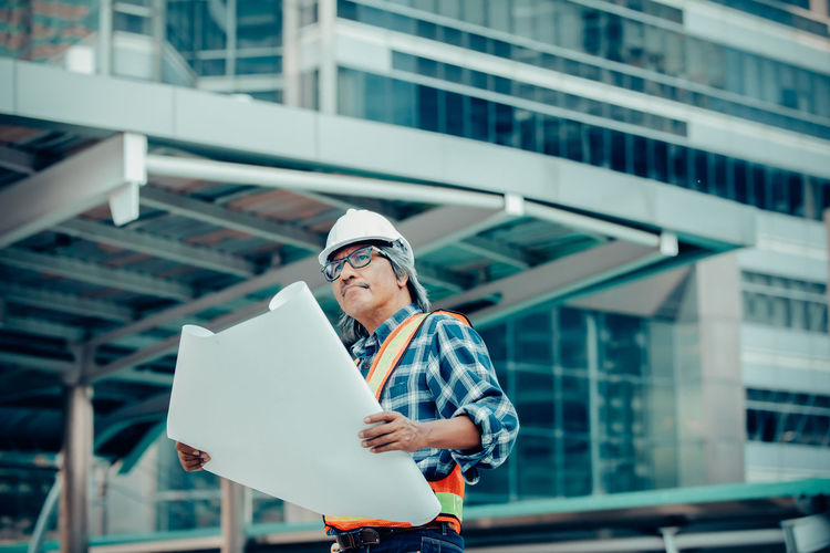 Manual worker with blueprint standing at construction site