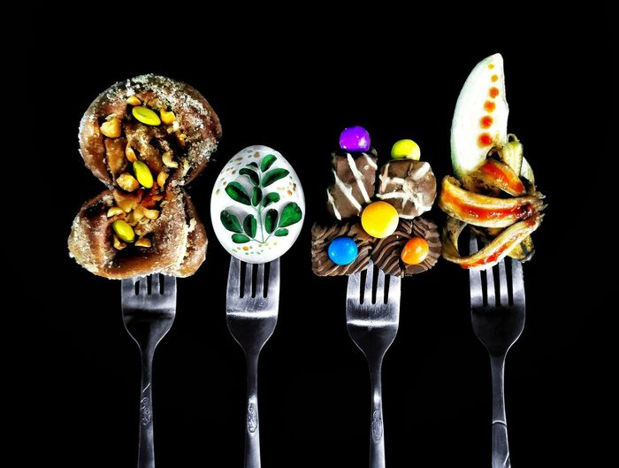 Close-up of forks with sweet food against black background