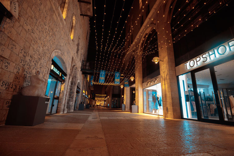 Low angle view of illuminated alley amidst buildings at night