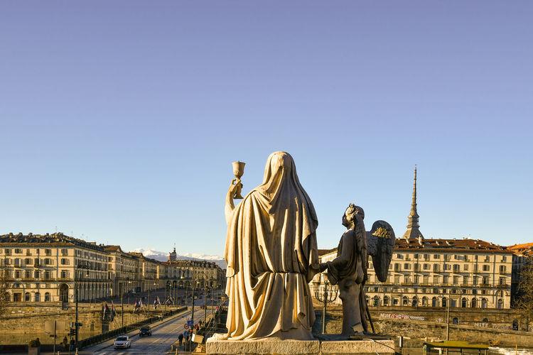 Statue in front of gran madre di dio church with the mole antonelliana in the background