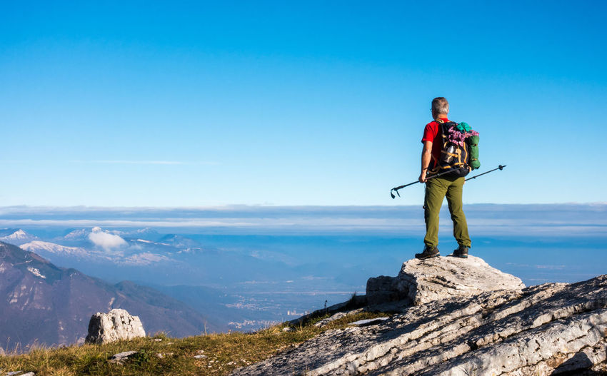 Hiker on the top in mountains. Travel sport lifestyle concept. Success Mountain Sky Standing Beauty In Nature Scenics - Nature One Person Tranquil Scene Full Length Real People Lifestyles Day Tranquility Leisure Activity Non-urban Scene Blue Nature Mountain Range Rock Idyllic Looking At View Success Hiking Sport Adventure