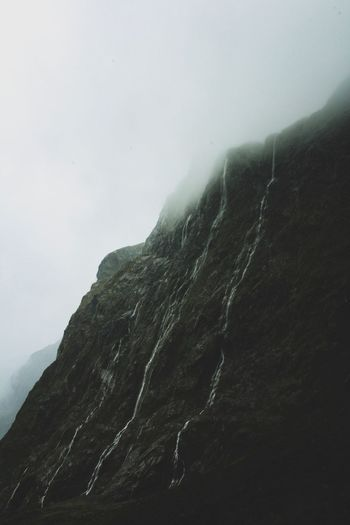 Low Angle View Of Mountain Against Sky During Foggy Weather