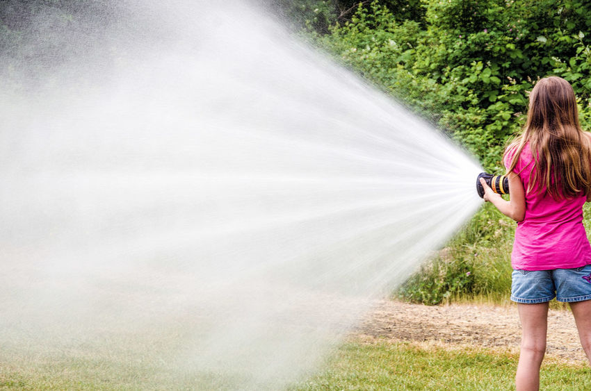 Dousing the Fire Casual Clothing Day Fire Hose First Eyeem Photo Full Length Grass Growth Hose Landscape Leisure Activity Lifestyles Motion Nature Outdoors Sky The Way Forward Tranquil Scene Tranquility Tree Water Spray