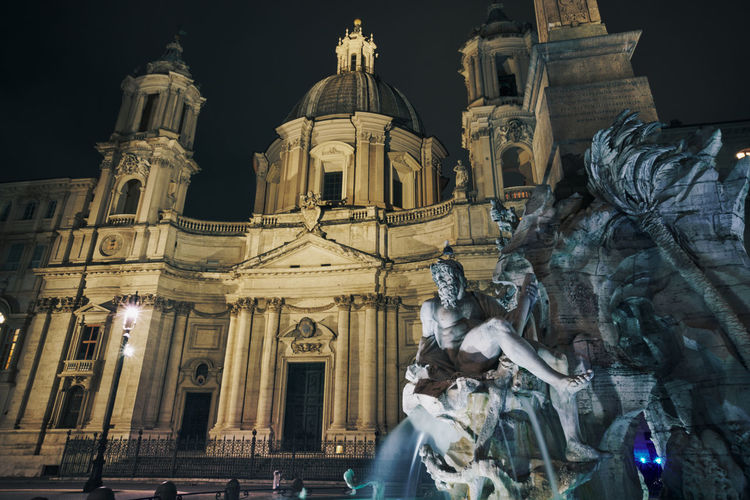 Low angle view of statue of historic building at night