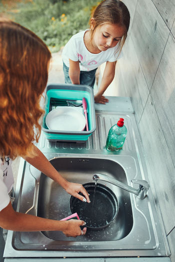 Teenager girl washing up the dishes pots and plates with help her younger sister