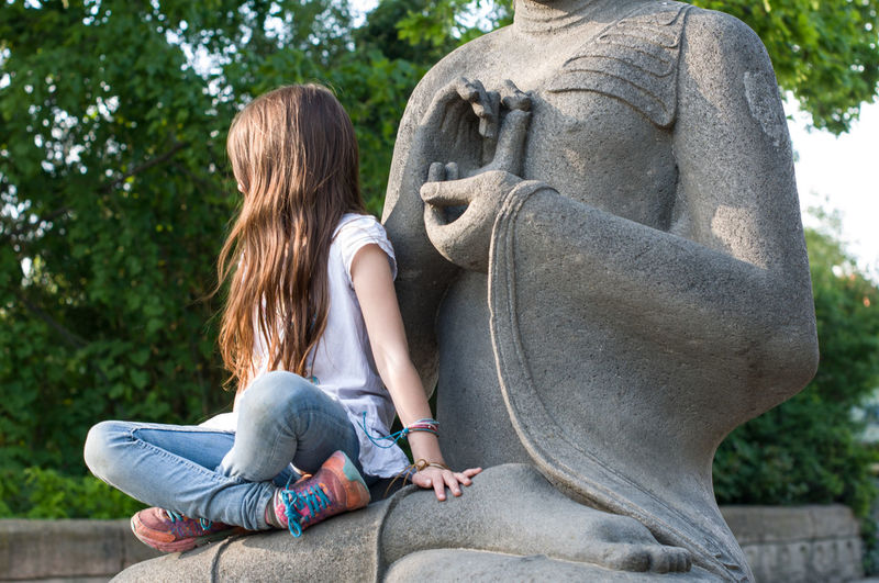 Rear view of girl sitting on statue