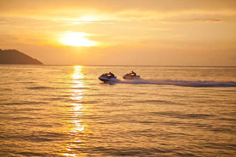People riding jet boats sea against sky during sunset