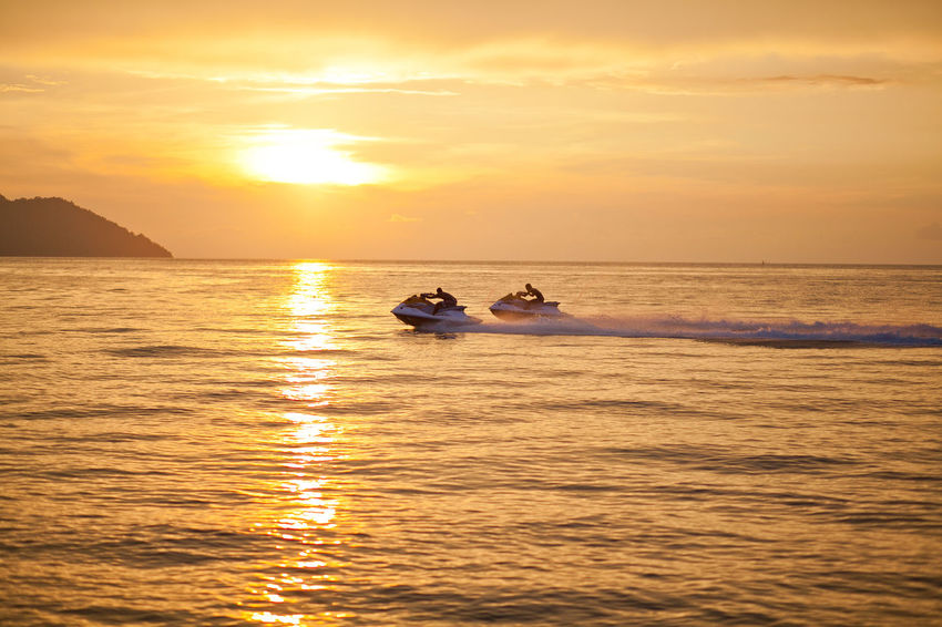 Man on Jet Ski having fun in ocean during sunset Sunset Water Nautical Vessel Sky Transportation Mode Of Transportation Sea Beauty In Nature Scenics - Nature Reflection Nature Waterfront Sunlight Orange Color Tranquility Cloud - Sky Travel Sun Outdoors Bright Jet Ski Fun Adventure Water Sport Golden Hour