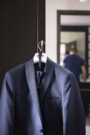 Blazer hanging on handle of cupboard at home