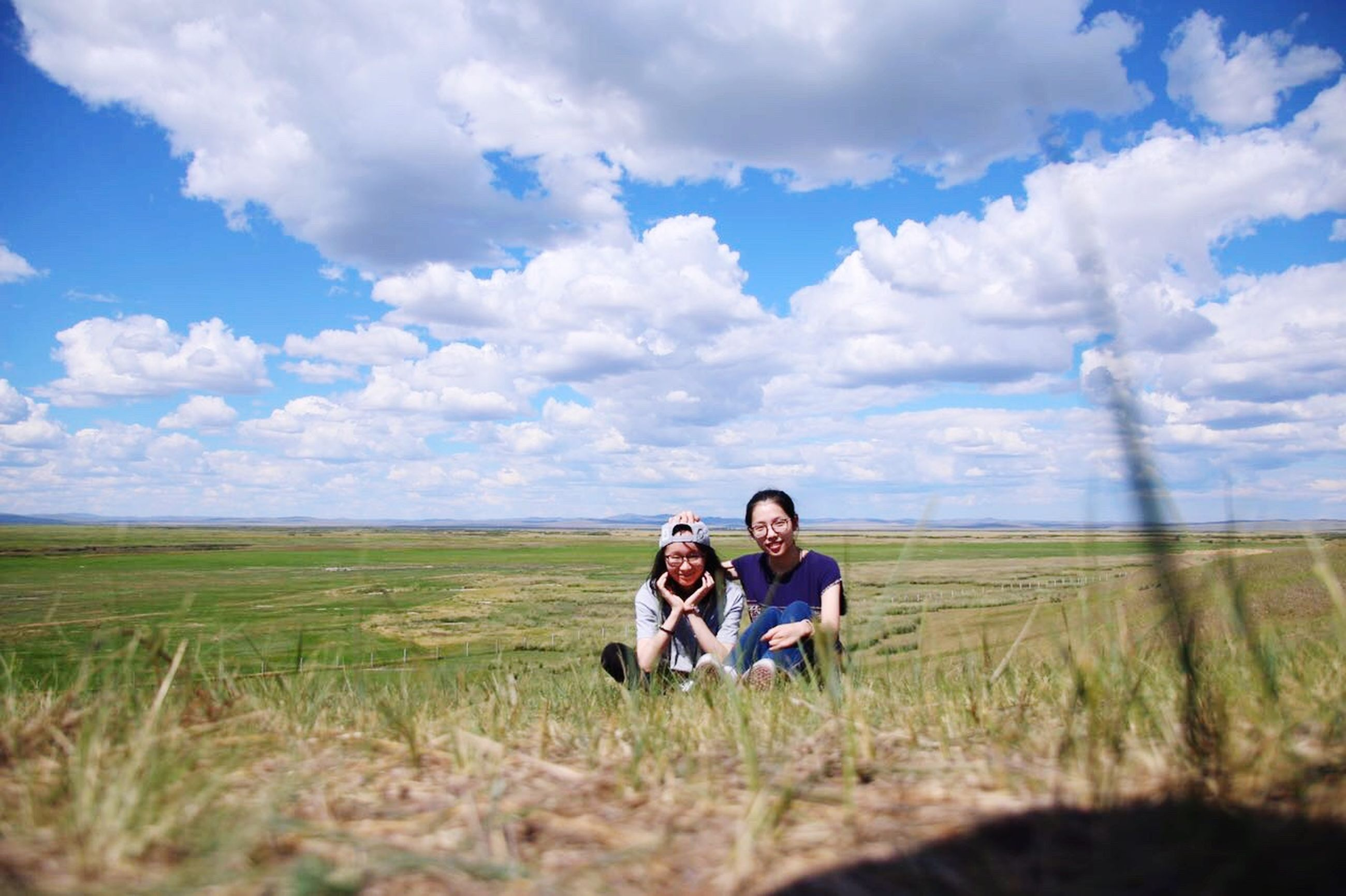 grass, sky, field, landscape, togetherness, cloud - sky, bonding, boys, grassy, family, love, day, casual clothing, friendship, rural scene, nature, tranquility, green color, surface level, horizon over land, person, outdoors, cumulus cloud, tranquil scene, single mother, growth, beauty in nature