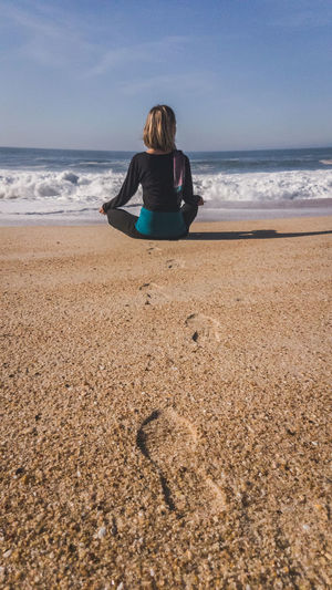 Rear view of woman practicing yoga at beach against sky