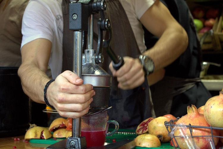 Man preparing pomegranate juice at counter