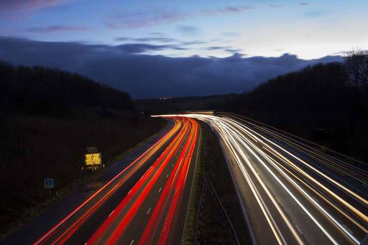 High angle view of light trails on two lane highway at dusk