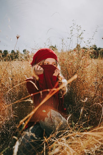 Beautiful woman covering face while sitting amidst plants