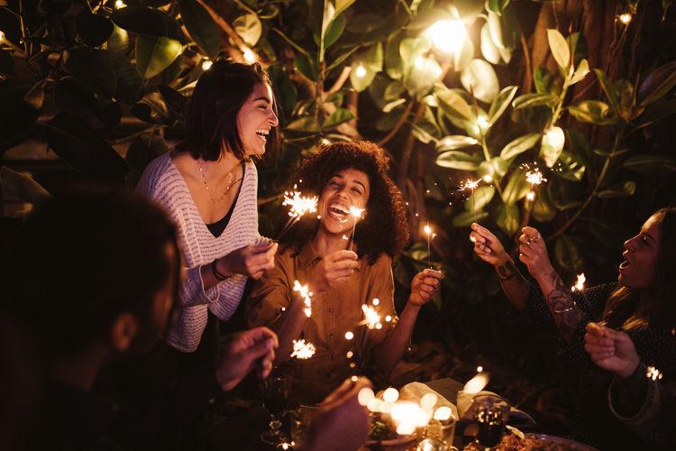 Group of people at illuminated christmas tree at night
