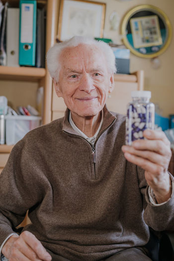 Smiling man holding medicines in bottle