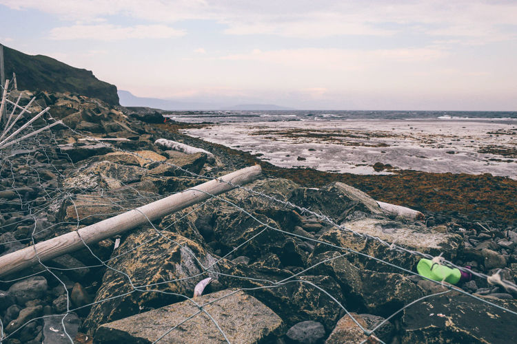 Barbed wire on rocky shore against sky