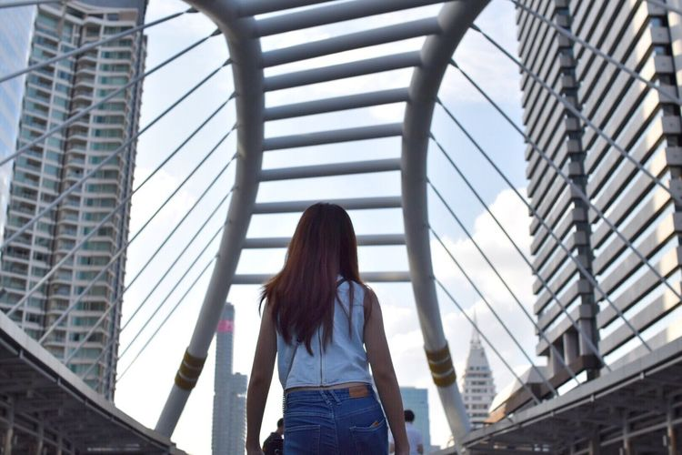 Rear view of woman walking  down chong nonsi bridge in bangkok thailand