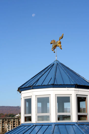 Low Angle View Of Weather Vane Against Blue Sky