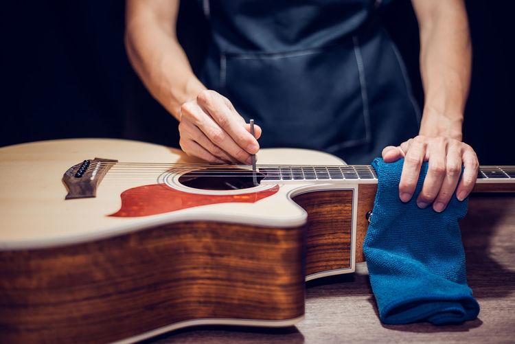 Midsection of man repairing guitar