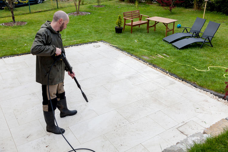 Man with pressure washer on the terrace in the garden. Blaster Clean Cleaner Cleaning Cleanser Cleansing Deck Dirt Dirty Garden Guy High-pressure Man Outdoors People Pressure Pressure Washer Purifier Real People Stone Terrace Tile Tiles Washer Water