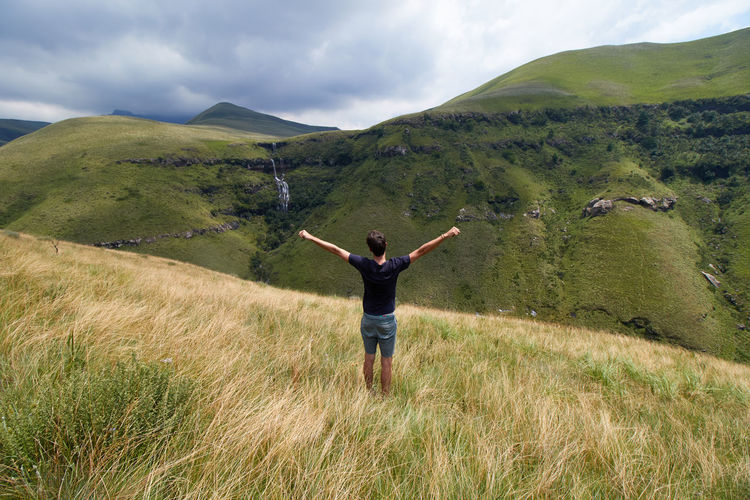 Man with open arms with a view of drakensberg