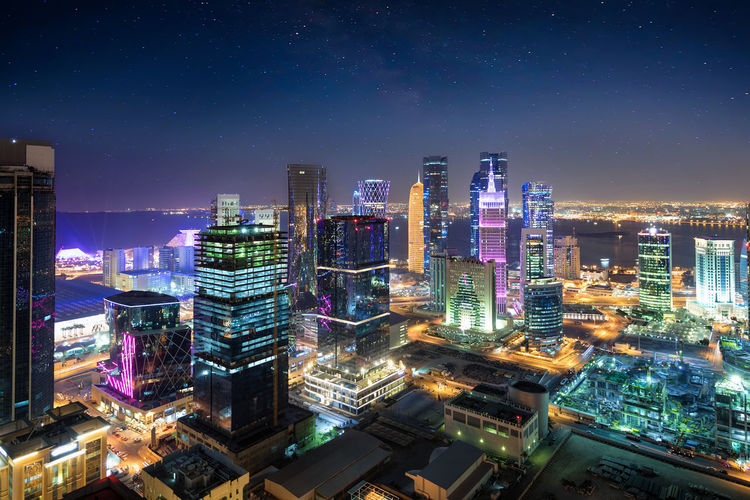 Panorama of the skyline of Doha, Qatar, during night with a starry sky Center Doha Lights Middle East Westbay Architecture Building Building Exterior Built Structure City City Life Cityscape Financial District  Illuminated Landmark Modern Night Office Building Exterior Qatar Sky Skyscraper Starry Stars Tall - High Urban Skyline