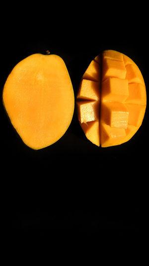 Close-up of orange slice over black background