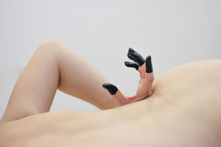 Midsection of shirtless woman lying down against white background