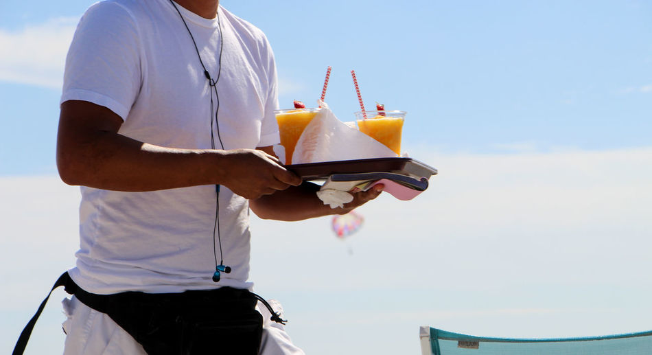 Midsection Of Waiter Carrying Drinks In Tray Against Sky On Sunny Day