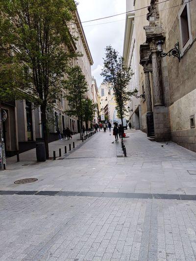 People on footpath amidst buildings in city