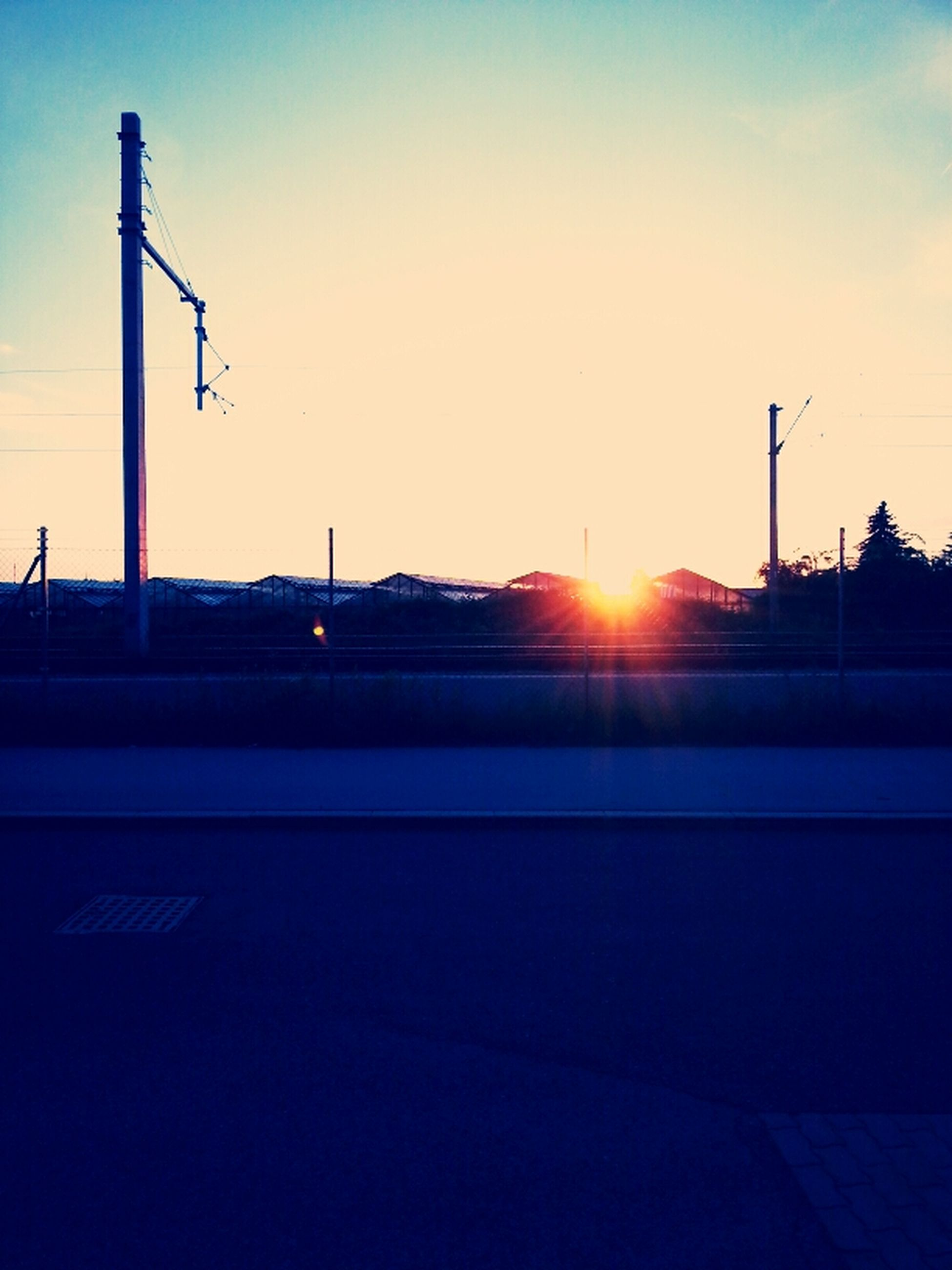sunset, sun, silhouette, street light, sunlight, orange color, sunbeam, sky, lens flare, clear sky, transportation, road, electricity pylon, built structure, copy space, building exterior, street, back lit, nature, outdoors