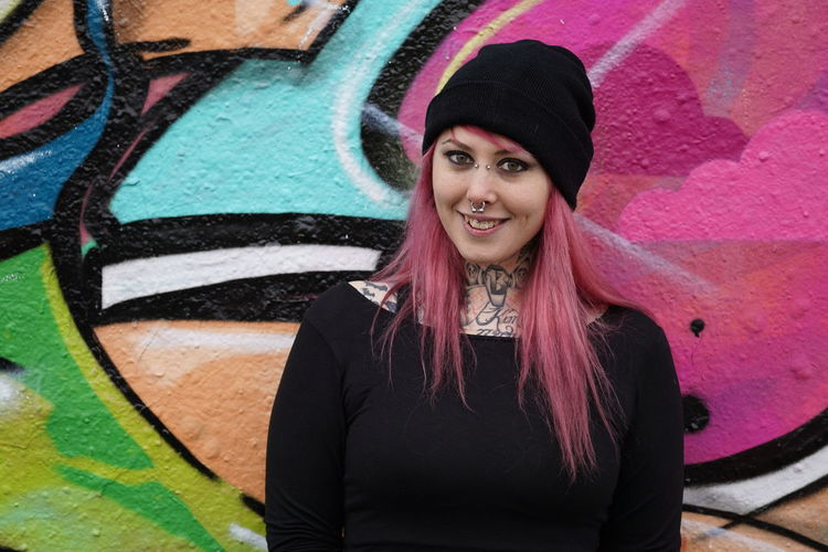 Alternative Casual Clothing Copy Space Emo Fashion Front View Girl Graffiti Happiness Lifestyles Long Hair Looking At Camera Person Pierced Pink Hair Portrait Punk Real People Smiling Tattooed Wall Woman Young Adult Young Women Youth