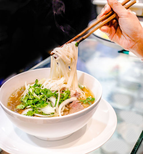 Cropped hand holding chopsticks over soup bowl