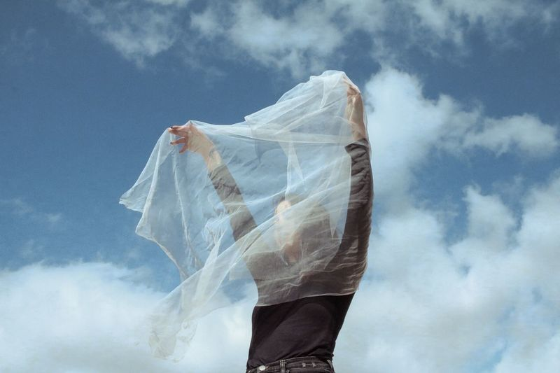 Woman holding white textile while standing against cloudy sky