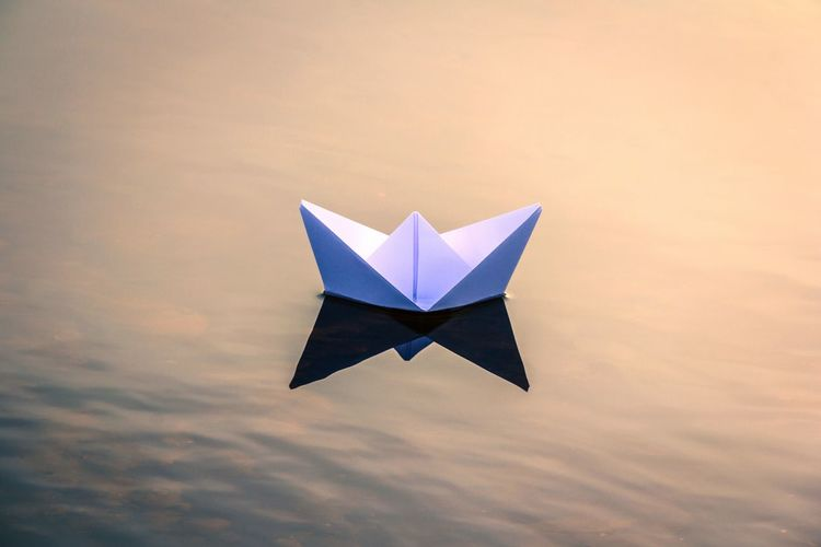 High angle view of white paper boat floating on lake during sunset