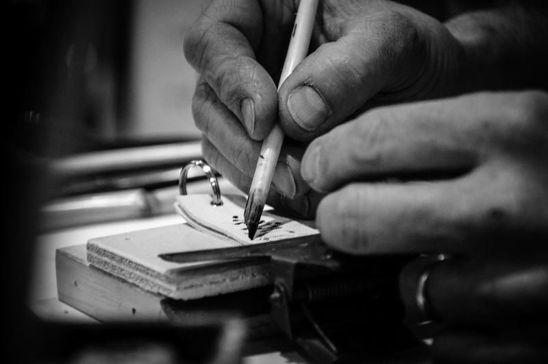 Cropped image of craftsperson writing on leather
