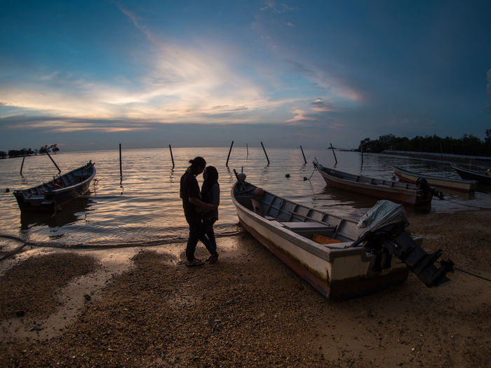 Couple Romancing At Beach Against Sky