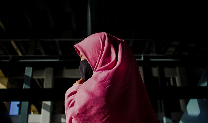 Low angle view of woman wearing hijab praying at home