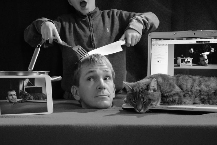 Boy Having Human Head Amidst Technologies With Cat On Table