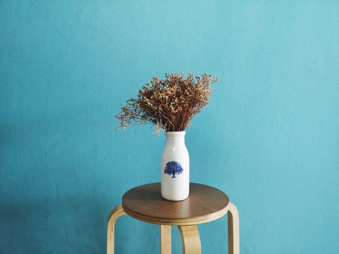 Close-up of vase on table against blue wall